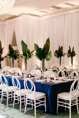 wedding reception long table navy blue linen white chair white flowers tall greenery tropical palms