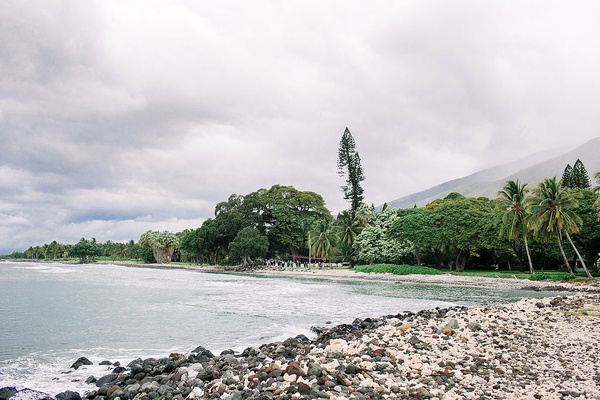 view of hawaiian venue plantation from sandbar white sand rocky coastline greenery cloudy