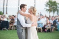 Bride in a Love Marley dress with lace bodice tulle skirt dances with groom in grey vest, pants,