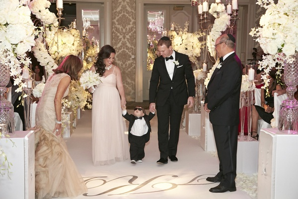 Cute little boy walking down aisle between couple