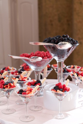 Wedding desserts of strawberry, blackberry, blueberry, cookie straws in martini glasses