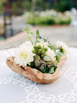 cocktail hour centerpiece made in dirftwood raw wooden bowl with white flowers and greenery
