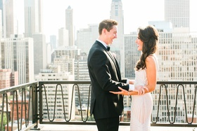Groom and bride holding each other's arms during first look on balcony in Chicago skyline