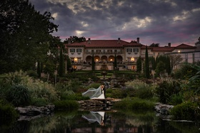 Philbrook Museum of Art wedding venue, bride's veil cascading while bride and groom kiss by pond