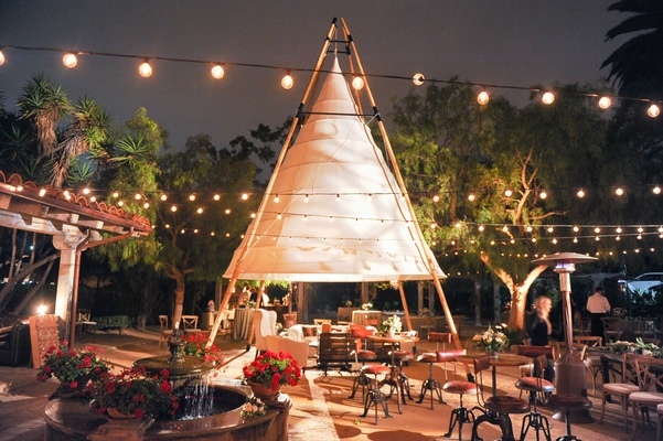 Night shot of courtyard wedding reception with large white teepee tepee tipi string globe lights