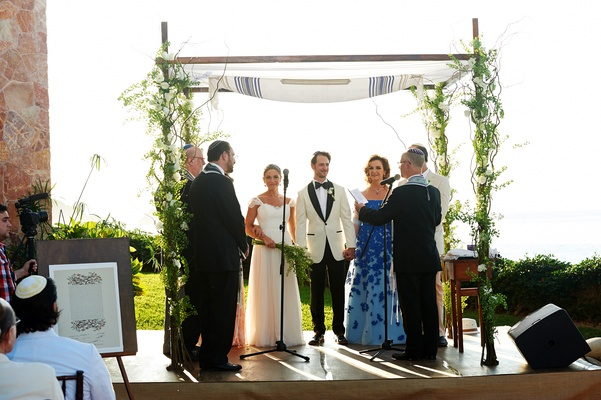 Bride and groom under tallit with greenery chuppah