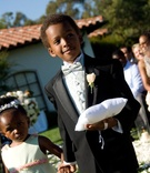 Ring bearer in tux holds pillow and hand of flower girl