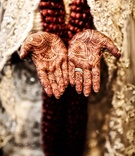 Bride wearing wedding rings with henna on hands