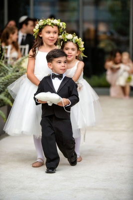 Ring Bearer holding ring pillow in tuxedo and flower girls behind white dresses flower crown ballet
