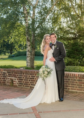 bride in flowing wedding dress with lace bodice and groom in tuxedo, brick pathway and birch trees