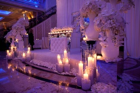Wedding reception with fabric draped alcove for bride and groom with white flowers and candles