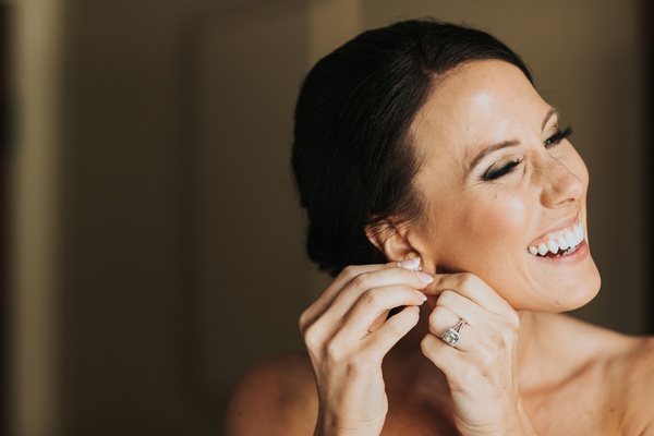 bride with low bun and side part puts on earrings