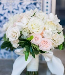 Soft wedding bouquet with white roses, pink roses, and green leaves wrapped with white bow