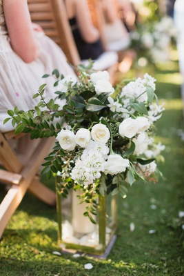 aisle decor, gold lantern with candle topped with white roses and greenery