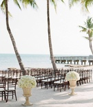 Ivory hydrangea and white rose in tan urn on sand at beach wedding ceremony in Key West, Florida