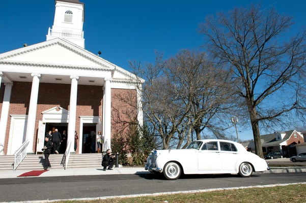 Classic white Bentley parked in front of a church