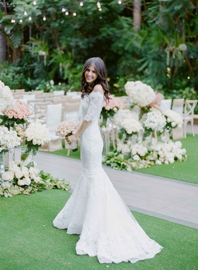 Bride in Marchesa lace wedding dress in front of ceremony decor white pink flowers garden ceremony