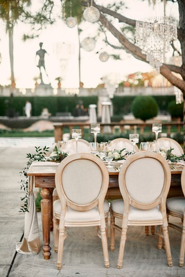 wedding reception with light wooden chairs with ivory ecru cushions