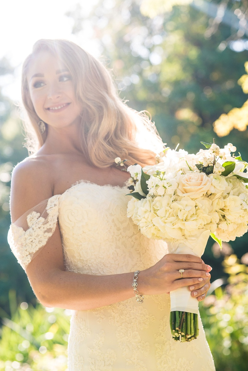 Bride holding white bouquet rose hydrangea greenery off shoulder lace wedding dress anne barge