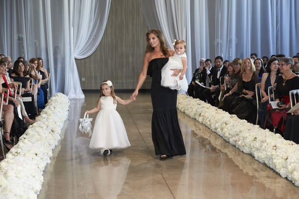 bridesmaid walks her daughters and flower girls down the aisle