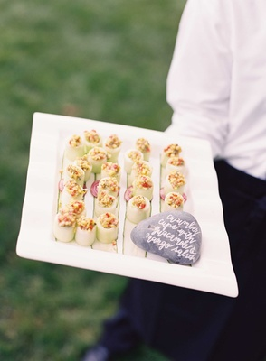 Cucumber cups with guacamole and mango salsa inside rock with calligraphy sign on tray