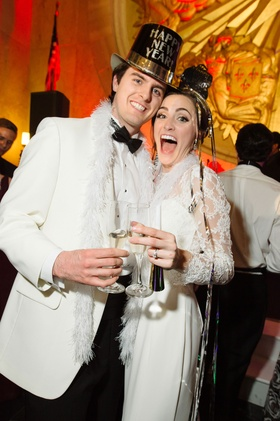 Wedding on new year's eve bride and groom in white with feather boa, champagne, and new year top hat