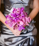 Bridesmaid in silver holding nosegay of orchids
