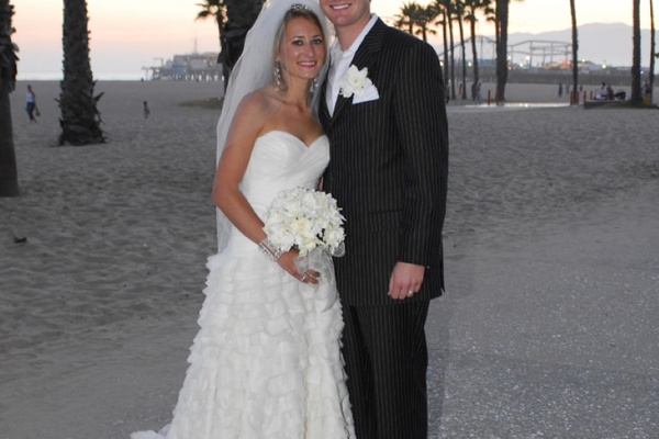 bride and groom stand on santa monica beach