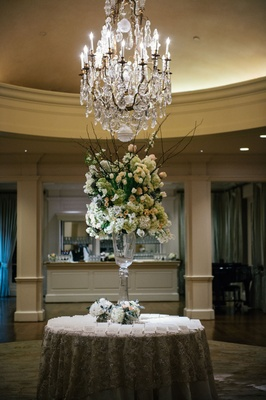 Wedding flowers branches ivory blush blooms greenery under chandelier wedding reception cocktail hou