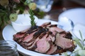 Ranch wedding table with platter of grilled beef tenderloin, sprig of rosemary