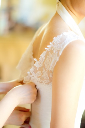 Bride gets help putting on her sleeveless Vera Wang dress with lace neckline