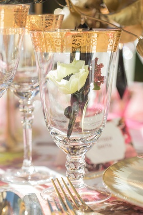 small white flower inside glass wine glass with gold detailing around gold flatware
