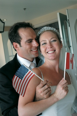 bride waves canadian flag and groom waves american flag