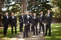 Groom and groomsmen in black tuxedos and white rose boutonnires