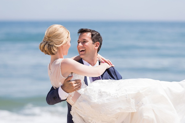 wedding portrait bride with blonde hair pretty updo groom holding her on beach in montauk