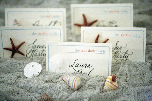 Escort cards in sand decorated with seashells