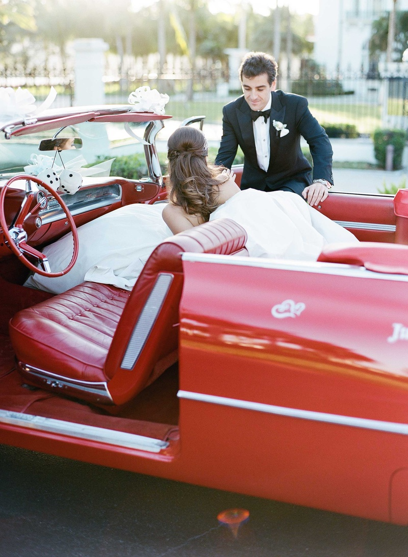 Groom in tuxedo helping bride out of classic red car with vintage seats and dice die hanging mirror