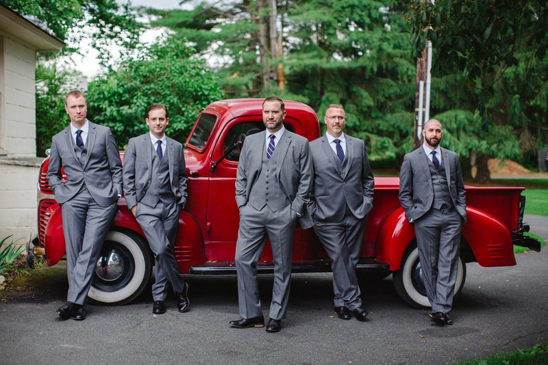 groom in custom grey brooks brothers suit with groomsmen in front of vintage red pickup truck