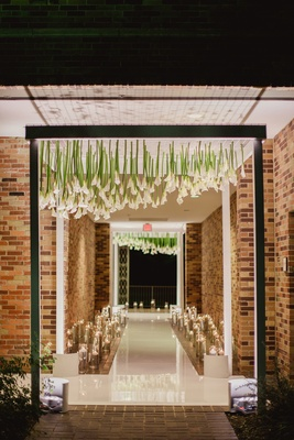 black archway with upside-down calla lilies to enter wedding reception
