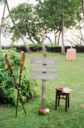 Tiki torches and wood signage in grass