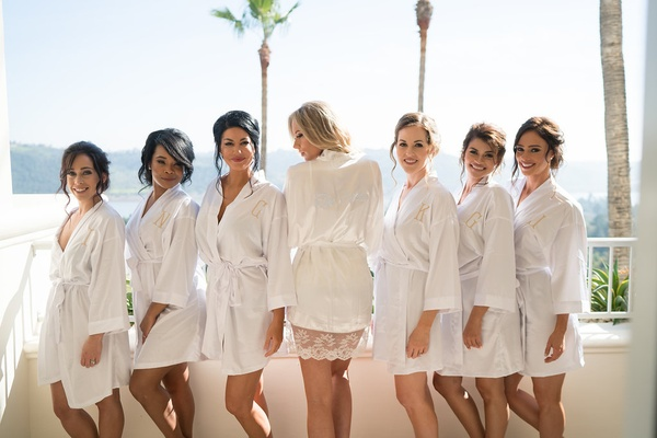 Stephanie Ming with bridesmaids in monogram white robes on balcony at wedding venue getting ready