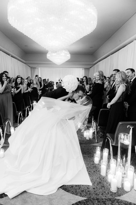 black and white photos of groom dipping bride for a kiss at the end of aisle