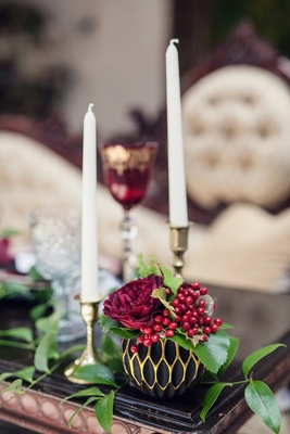 Wedding reception table with a round, black and gold honeycomb vase, red rose, viburnum berries