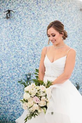 wedding portrait of bride v neck wedding dress necklace hair low bun ivory bouquet flowers by cina