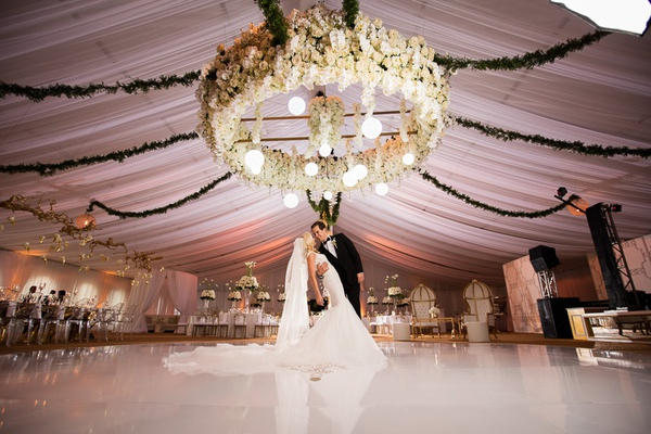 large orchid chandelier with round lights hanging down and garlands extending outward