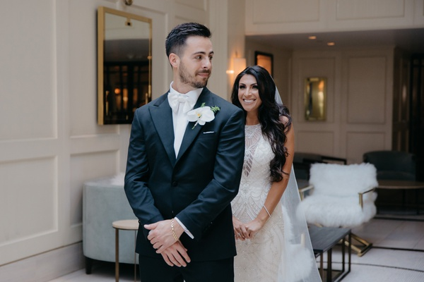 wedding first look photo, bride in maggie sottero wedding dress, groom in white tie tuxedo