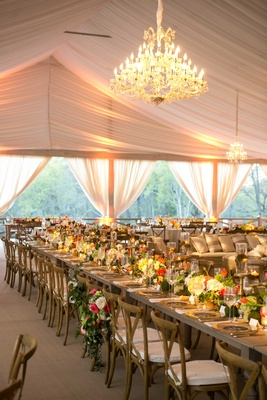 Blush tent wedding with chandeliers and rustic wood tables with low centerpieces