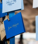 Blue and gold seating card assignments on ribbon