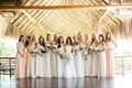Bridesmaids in mismatched cream and peach Amsale dresses for a beachside wedding celebration