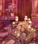 Tall glass candleholders with white rose centerpiece